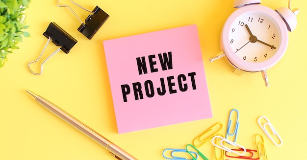 テキストが付いたピンクの紙newproject時計ペン