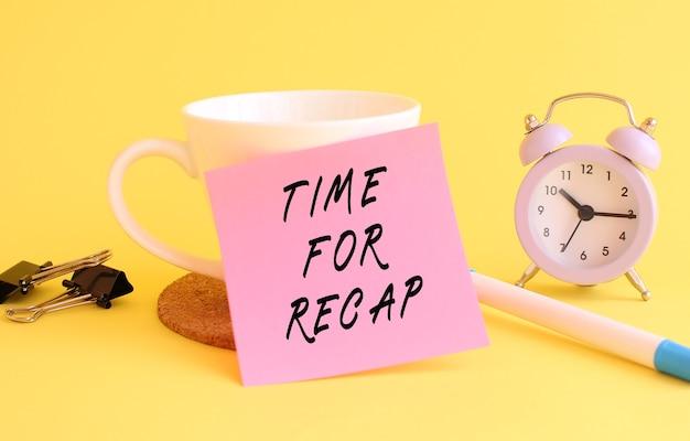 흰색 컵에 텍스트 time for recap와 함께 분홍색 종이. 시계, 노란색 배경에 펜입니다.
