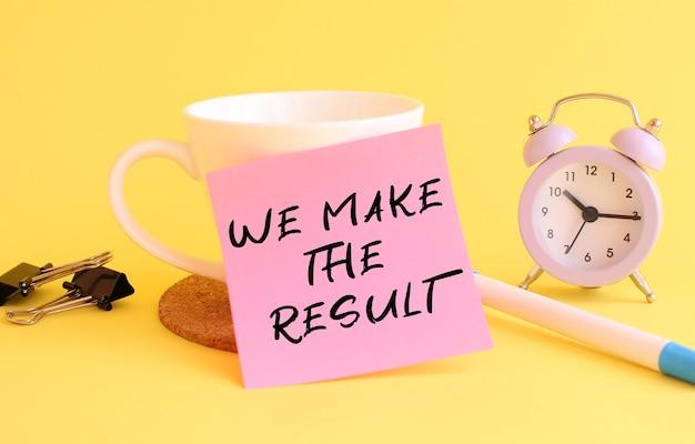 Розовая бумага с текстом мы делаем результат на белой чашке. часы, ручка на желтом фоне. концепция дизайна.