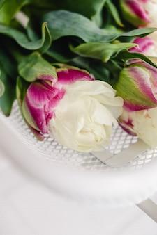 緑の茎と葉が白い純金属バスケットで横になっているピンクのオウムチューリップ