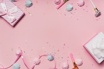 Pink party background with candies; party blowers and curl ribbon