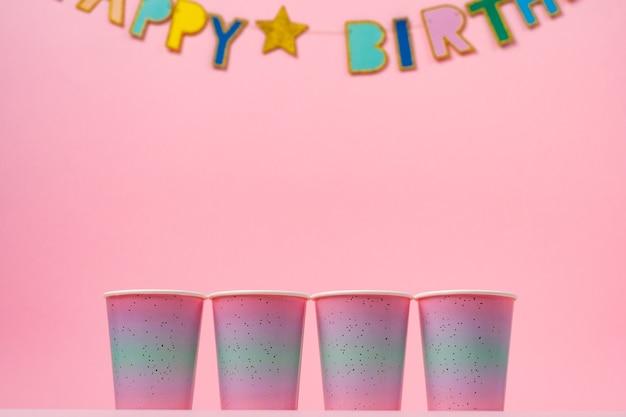 핑크 생일 화 환과 핑크 파티 컵을 닫습니다.