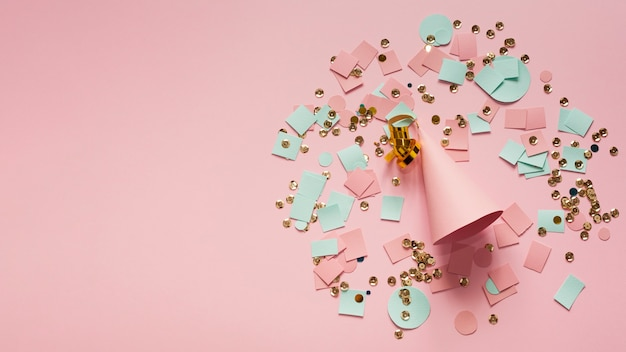 Pink party hat surrounded by confetti and paper