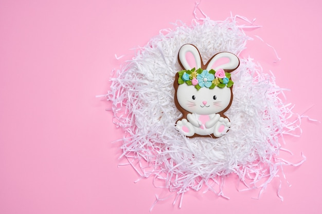 Pink pastel background with easter bunny cookie
