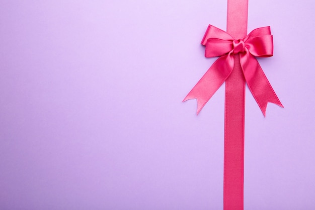 Pink pastel ribbon with bow isolated on purple background. top view.