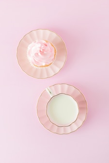 Pink pastel vertical banner with decorated cupcakes, cup of coffe with milk