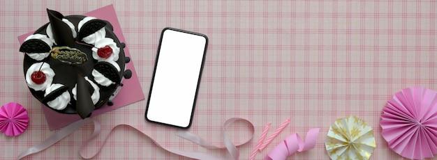 Розовый фон с смартфон и торт