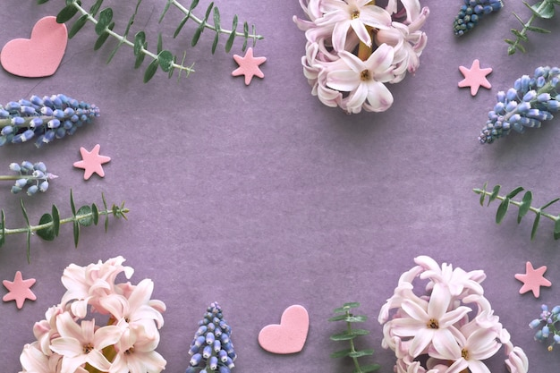 Pink pearl and blue grape hyacinth flowers with decorative hearts on purple paper, copy-space.