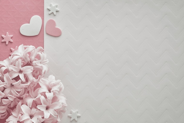 Pink pearl hyacinth flowers on colored background with decorative hearts, copy-space