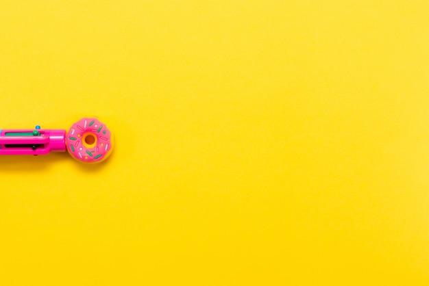 黄色の背景に分離されたドーナツの形のピンクのペン色とりどりのペン学校に戻る