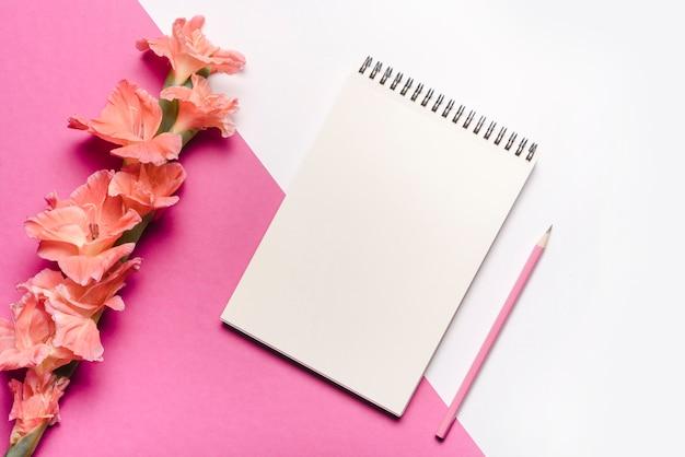 ピンクの鉛筆;ピンクと白の二重の背景に美しい花と空の渦巻のメモ帳