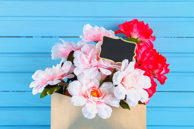 Pink peonies in a craft package with a chalkboard on a blue wooden table. postcard for the holiday.