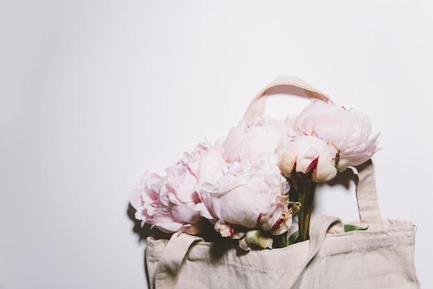 Pink peonies flowers in the cotton bag on white background