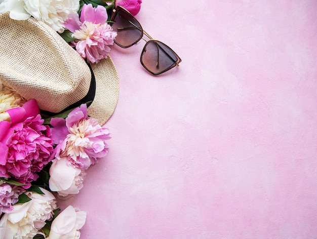 Pink peonies and hat on a pink concrete background