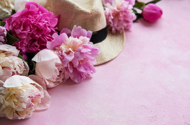 Pink peonies and hat on a pink concrete