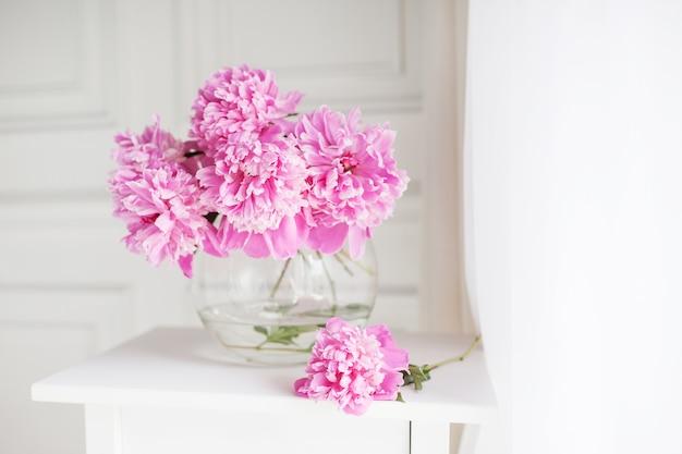 Розовые пионы в стеклянной вазе. цветы на белом столе возле окна. утренний свет в комнате. красивый цветок пиона для каталога или интернет-магазина. цветочный магазин и концепция доставки. баннер. копировать пространство