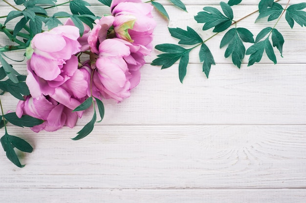 Pink peonies and leaves on wooden background