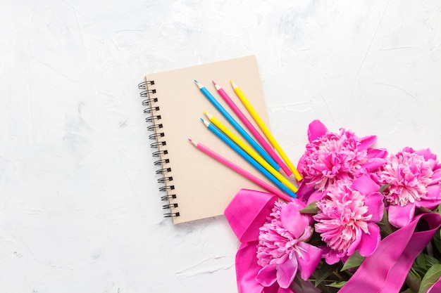 Pink peonies, a notebook and bright colored pencils on a light stone
