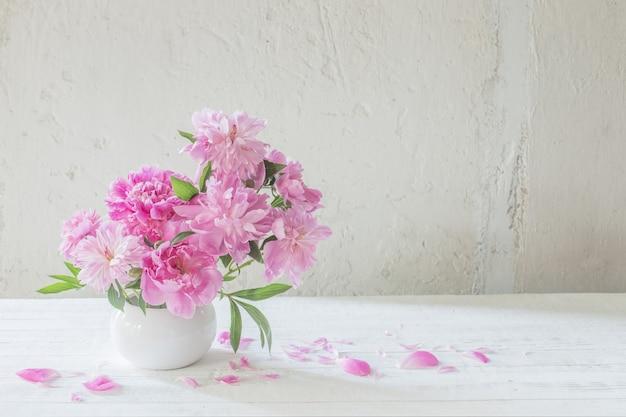 Розовые пионы на старой белой стене