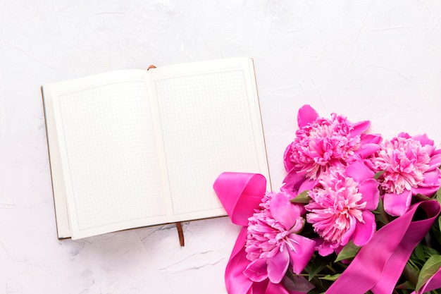 Pink peonies and an open diary on a light stone