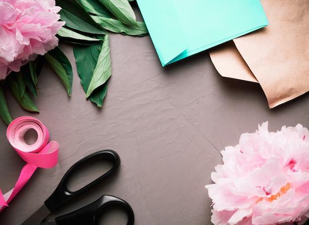 Розовые пионы, лента, ножницы, крафт-бумага, конверт расположены вокруг на сером фоне.
