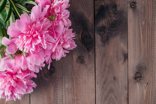 Pink peonies on wooden background, copy space