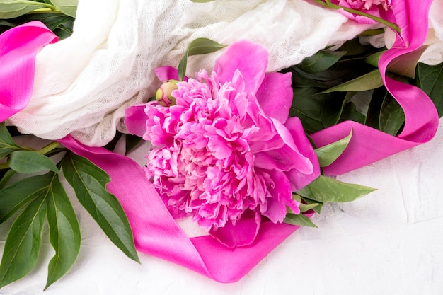 Pink peonies wrapped in a white fabric with a pink ribbon on a light stone