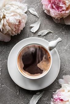 ピンクの牡丹と灰色のコンクリートの背景に美しいスタイルのコーヒーのカップ