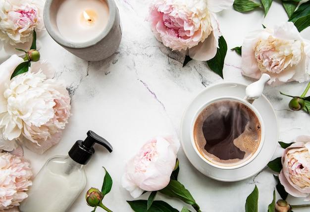 ピンクの牡丹と白い背景の上の美しいスタイルのコーヒーのカップ