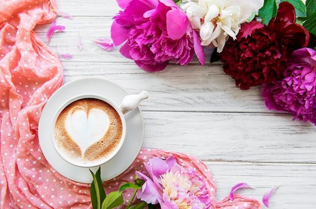 ピンクの牡丹と白い木製の背景に美しいスタイルでコーヒーのカップ花の背景上面図