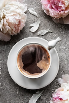Pink  peony and cup of coffee  in beautiful style on grey concrete background