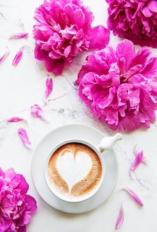 Pink peony and cup of coffee in beautiful style on white marble table.