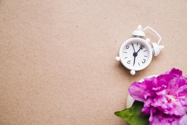 종이 질감 골 판지 배경에 흰색 알람 시계와 꽃병에 분홍색 모란 꽃