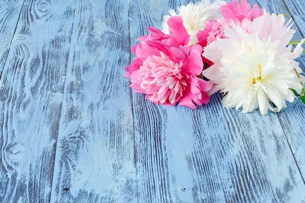 인사말 메시지 복사 공간 어두운 소박한 나무 배경에 분홍색 모란 꽃. 어머니의 날과 봄 배경 개념