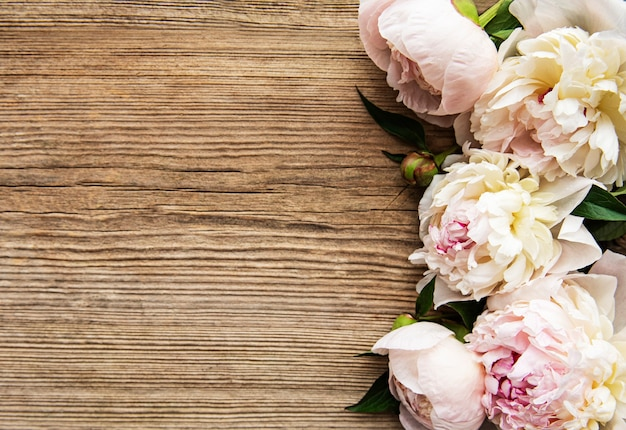 Pink peony flowers as a border on a old wooden surface