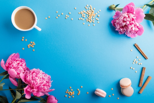 Pink peony flowers and a cup of coffee on blue pastel