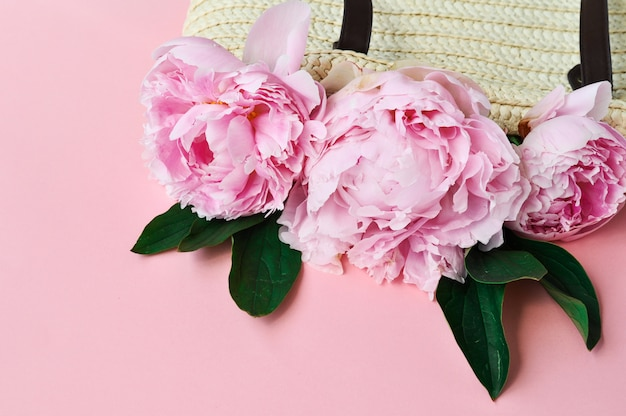 Pink peony flowers in summer woven straw bag on pink.