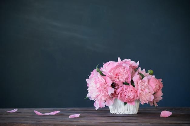 Розовый пион в корзине на фоне темной стены