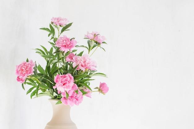 배경 오래 된 벽에 세라믹 꽃병에 분홍색 모란