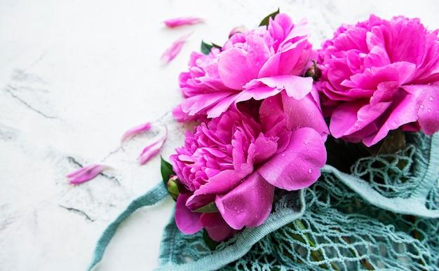白い大理石のテーブルの上のストリングバッグのピンクの牡丹。フラットレイ