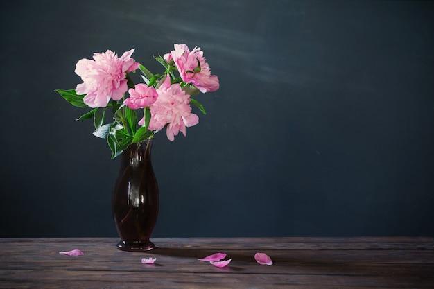 Розовый пион в вазе на фоне темной стены