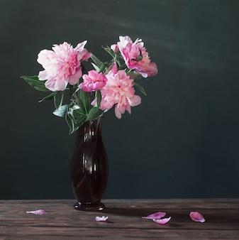 背景の暗い壁に花瓶のピンクの牡丹