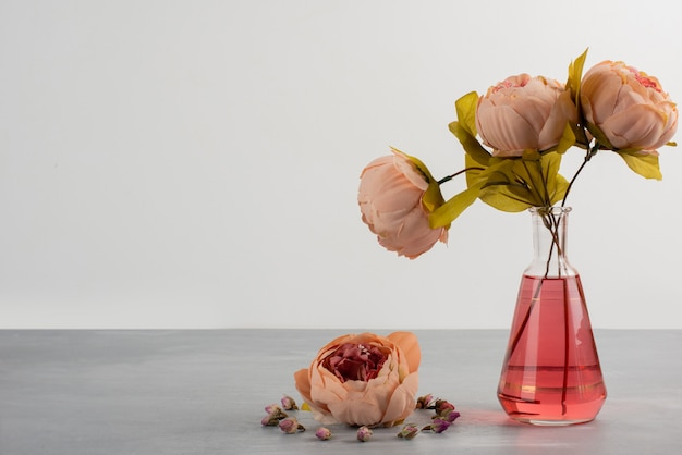 Pink peony rose flowers in glass vase on gray table