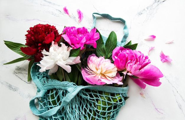 Pink peony in string bag  on white marble surface