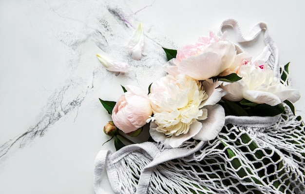 Pink peony in string bag  on white marble. Premium Photo