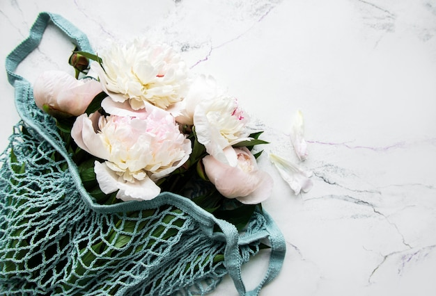 Pink peony in string bag  on white marble.