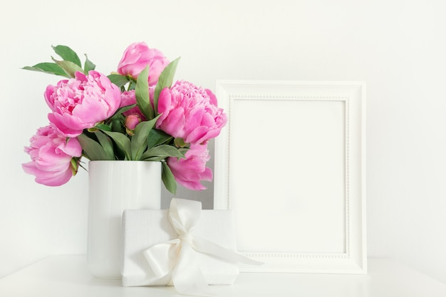 Pink peony in vase with gift photo frame on white.