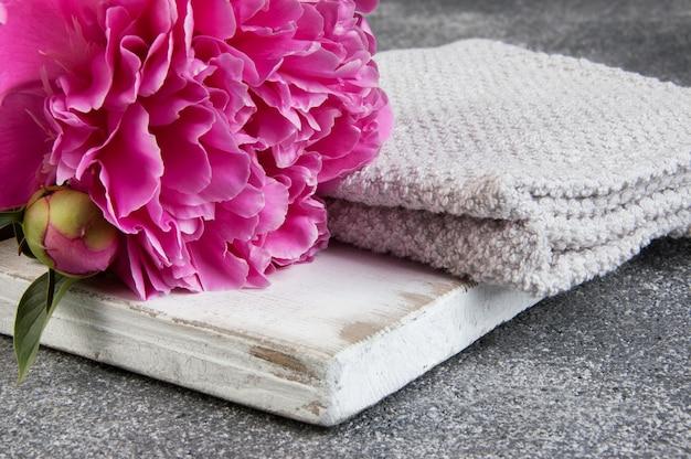 ピンクの牡丹、ホワイトボード、灰色の背景にタオル