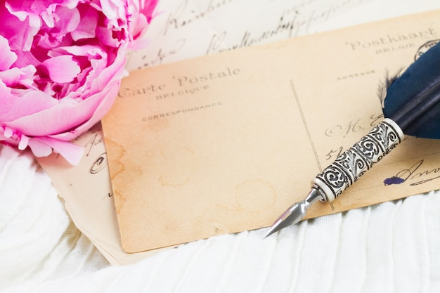 Pink peony with antique blank letter with copy space and feather pen on white lace