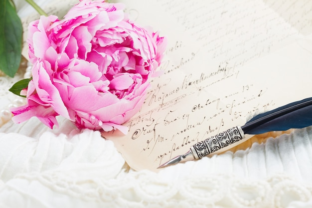 Pink peony with antique handwritten letter and feather pen